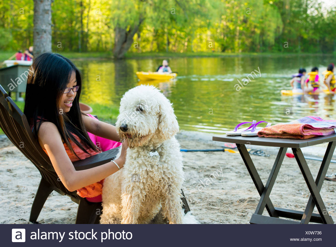 Girl sitting on chair by lake with dog Stock Photo