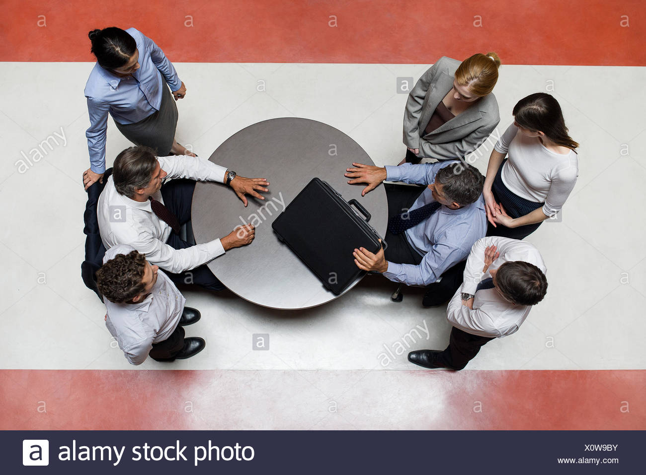 Businessman flanked by support staff considers opponents offered deal - Stock Image