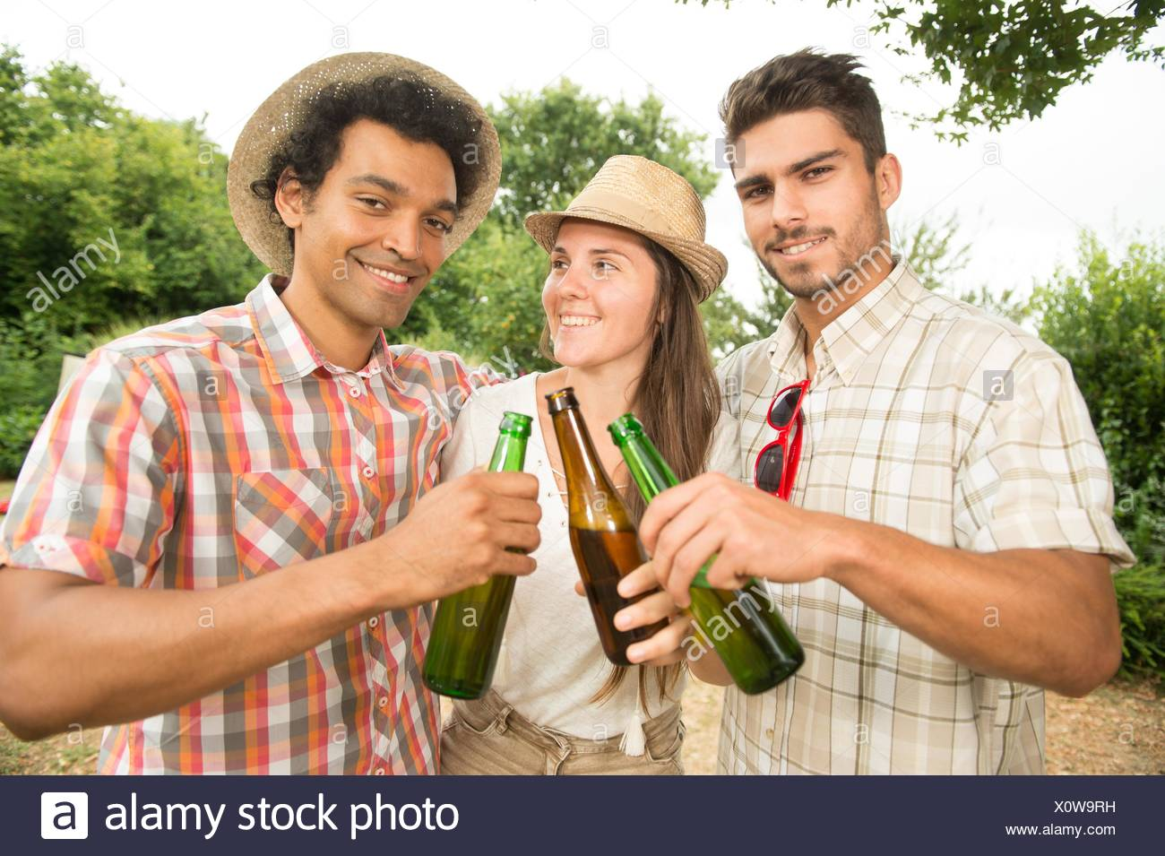 Group of friends toasting a beer bottle while preparing barbecue grill in park, France. Stock Photo