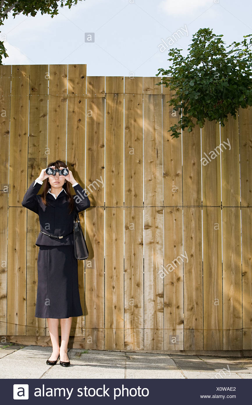 A businesswoman looking through binoculars - Stock Image