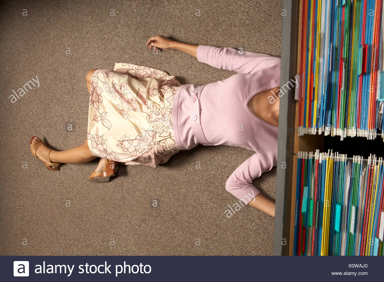 High angle view of a businesswoman lying under a filing cabinet drawer Stock Photo