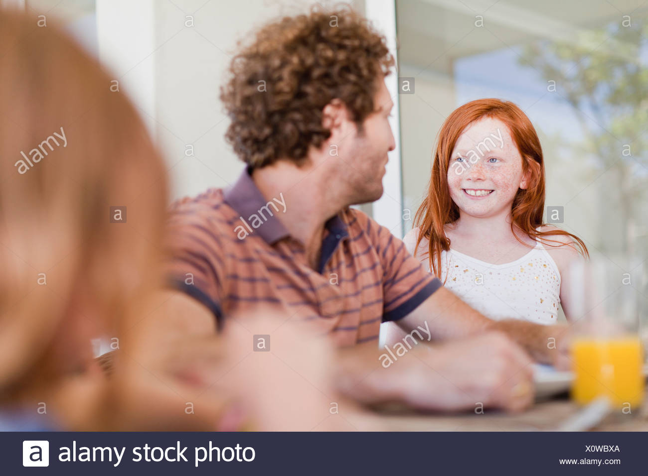 Girl smiling at father at breakfast - Stock Image