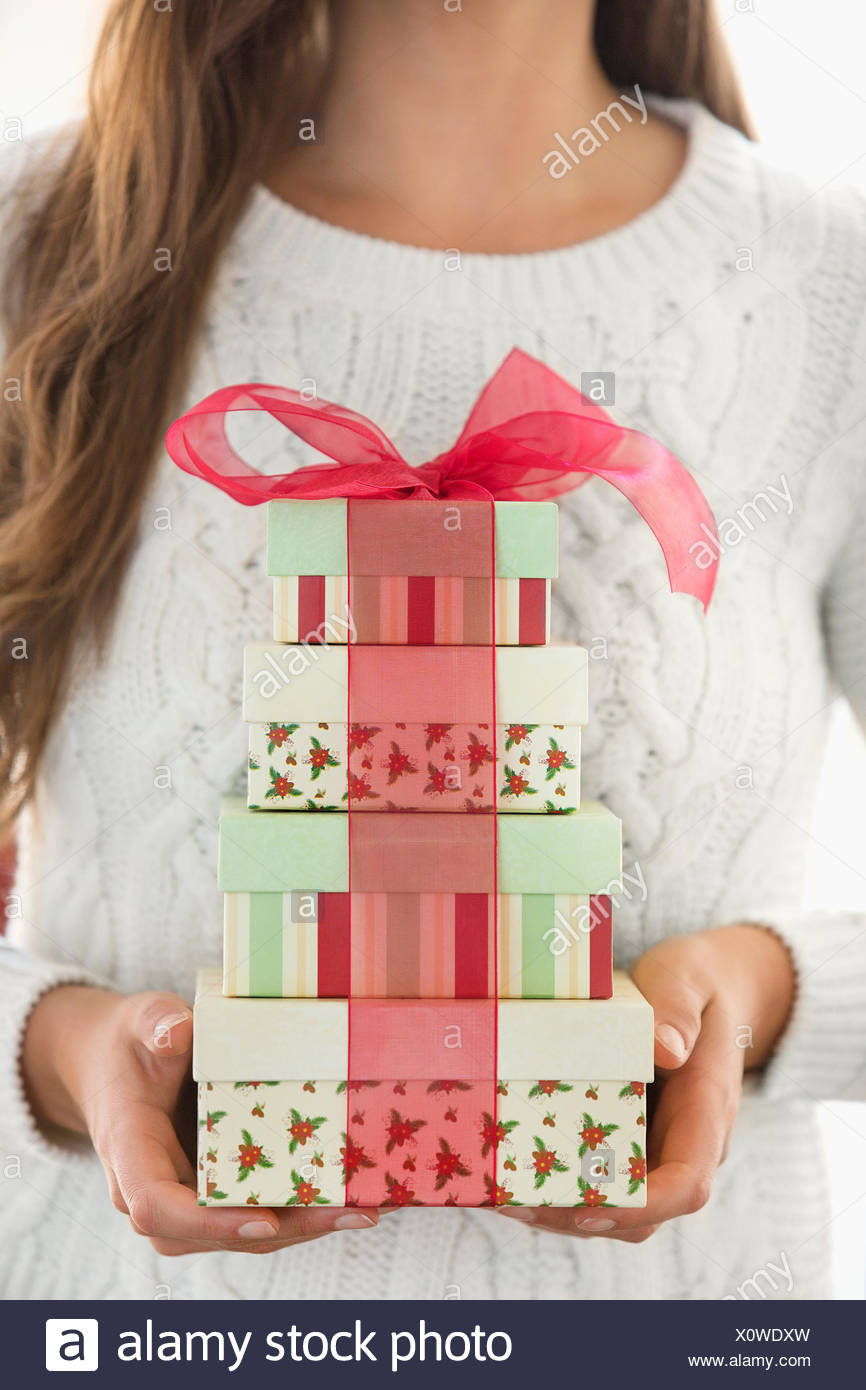 Woman holding stack of Christmas boxes - Stock Image