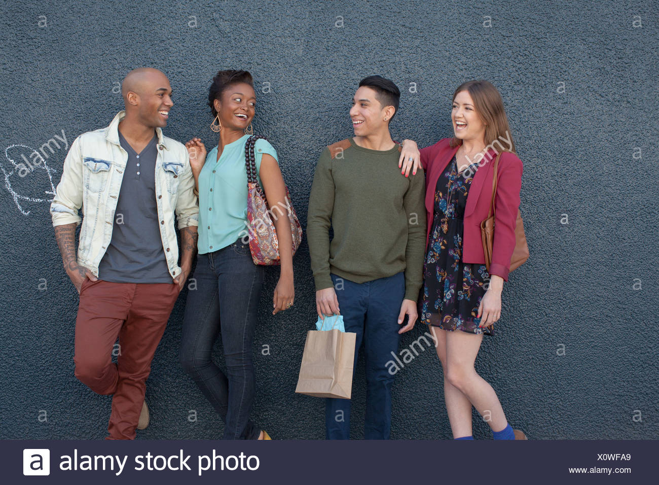 Four friends by grey wall - Stock Image