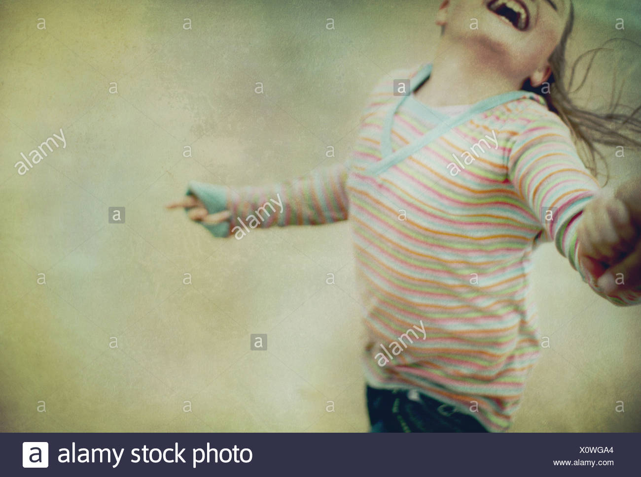 girl swinging round with a smile - Stock Image