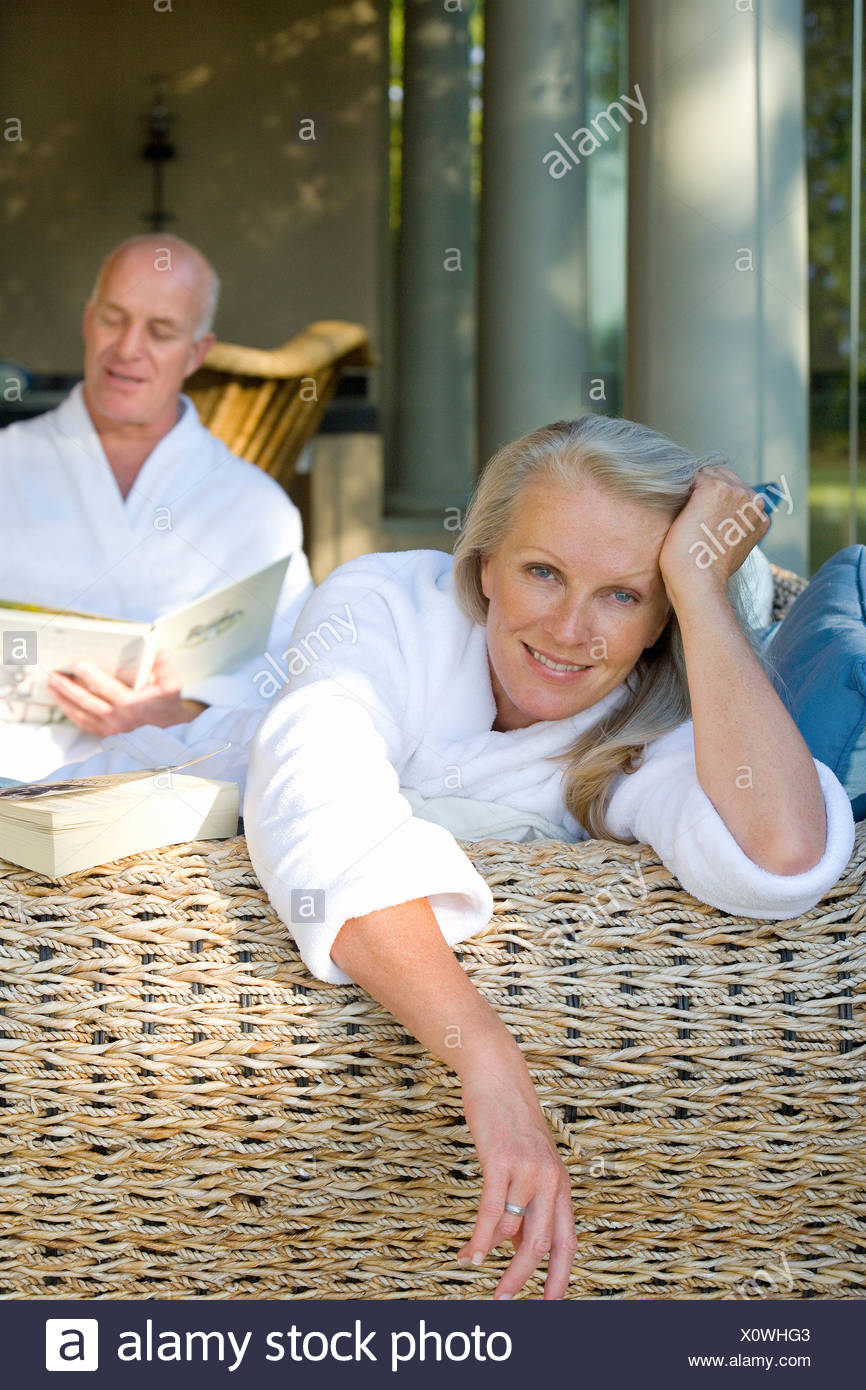Mature couple wearing white bath robes on wicker chair, portrait of woman smiling - Stock Image
