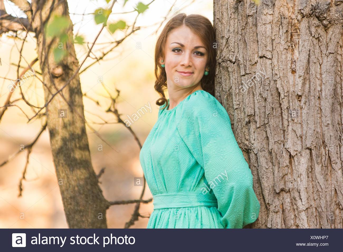 Young beautiful girl in a long dress walking in the woods on a warm summer day. Stock Photo