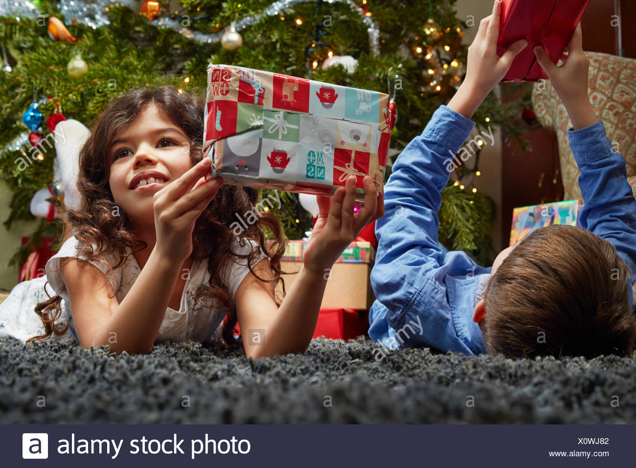 Sister and brother lying in sitting room holding up christmas gifts - Stock Image