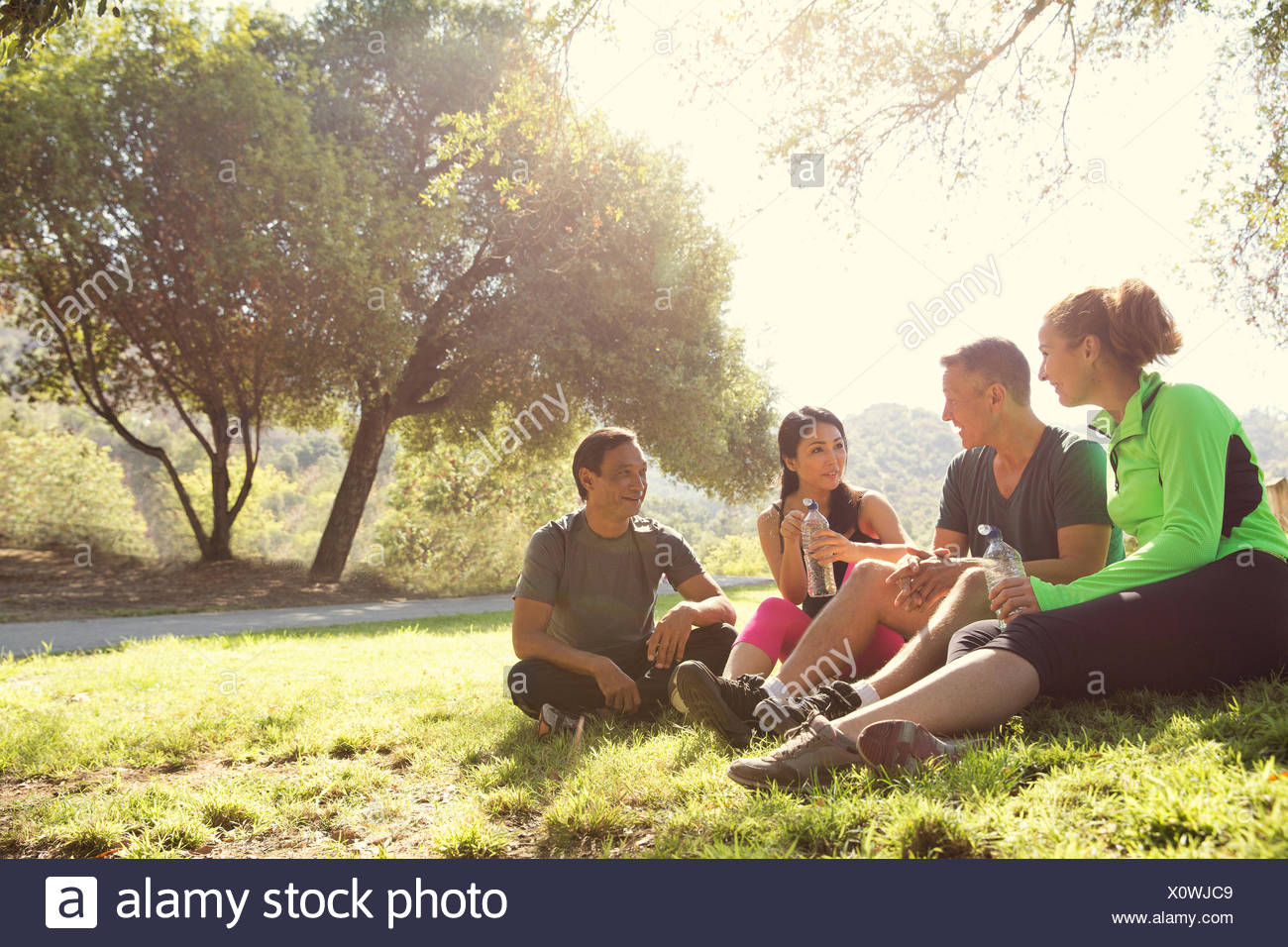 Four mature male and female runners sitting chatting in park - Stock Image