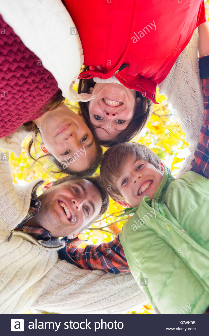 Happy family in a group huddle, looking at camera - Stock Image