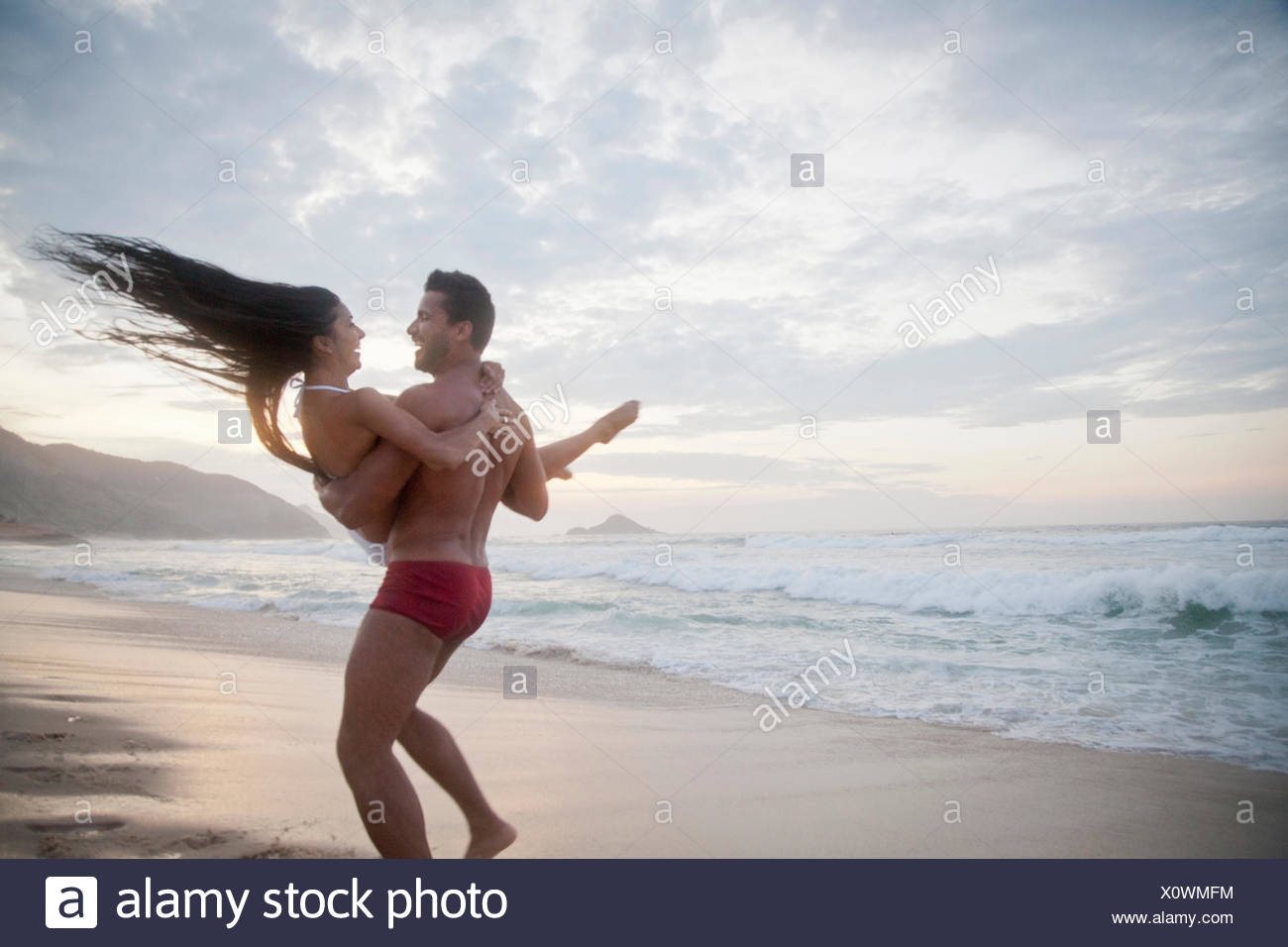 Mid adult couple on beach, man carrying woman in arms, rear view - Stock Image