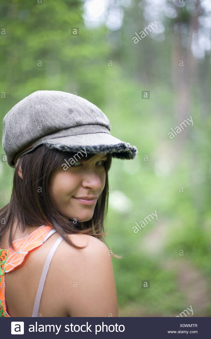Native American female teenager smiling while walking in woods. - Stock Image