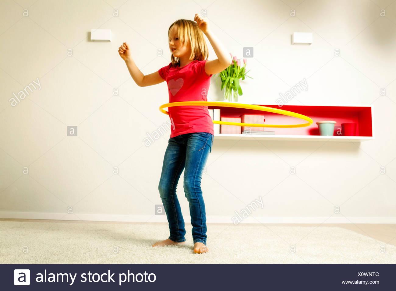 Girl using hula hoop in living room, Munich, Bavaria, Germany - Stock Image