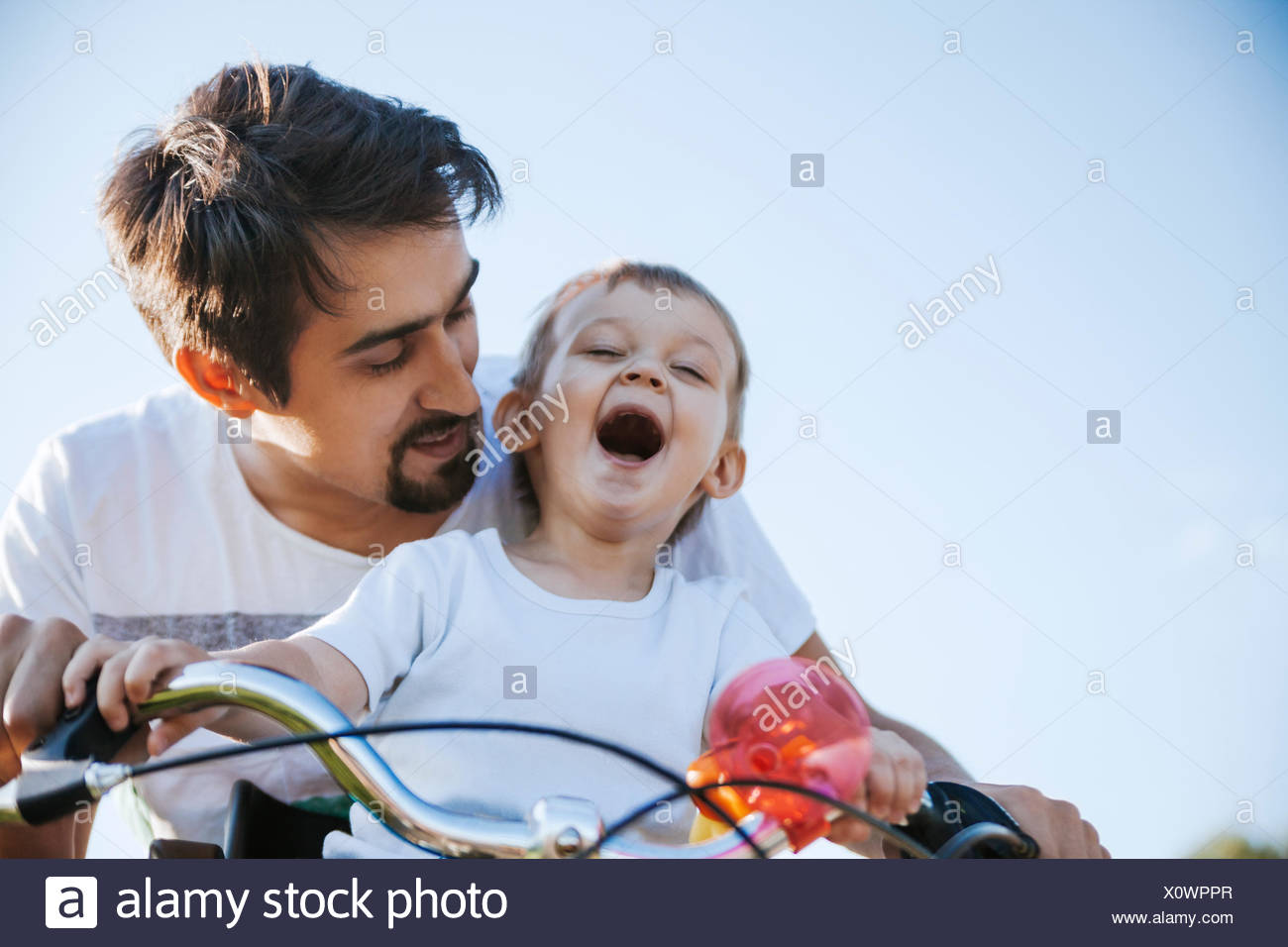 Laughing little boy on bicycle tour with his father - Stock Image