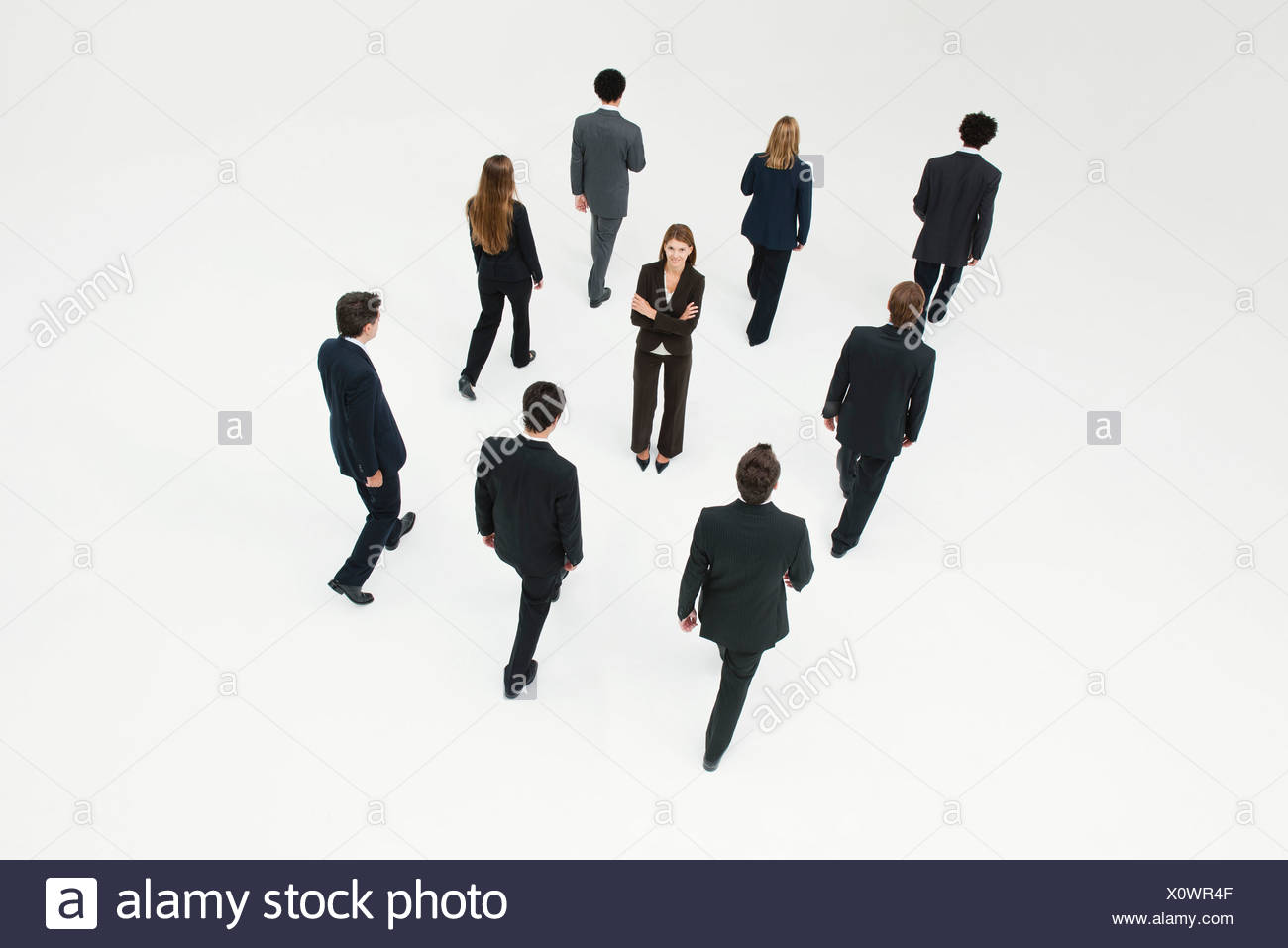 Businesswoman standing in midst of other anonymously dressed business professionals - Stock Image