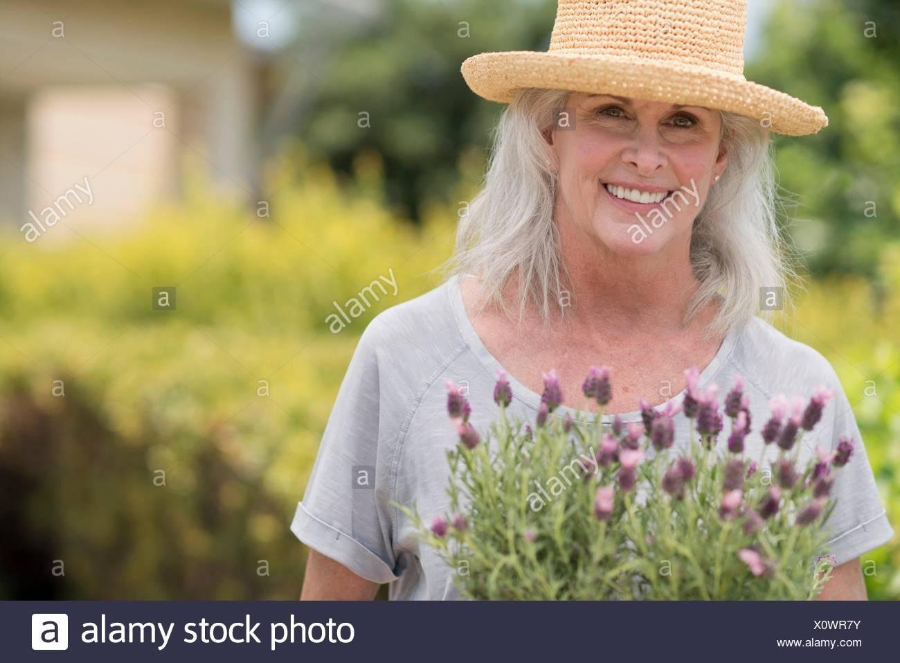 Senior woman holding pot plant. - Stock Image