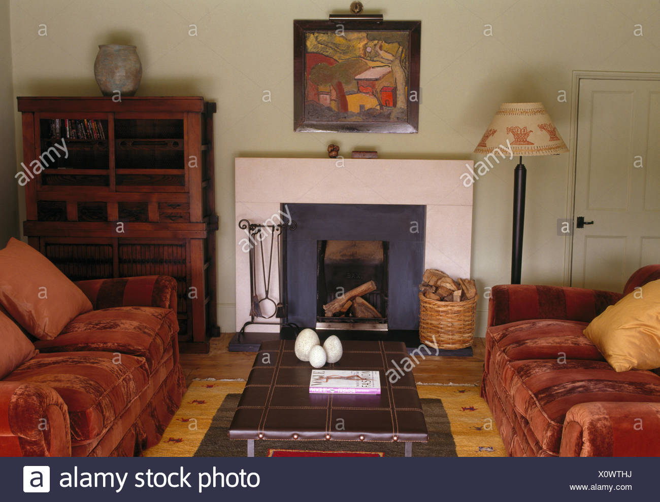 Brown velvet sofas on either side of tile topped coffee table in front of fireplace in forties style living room - Stock Image
