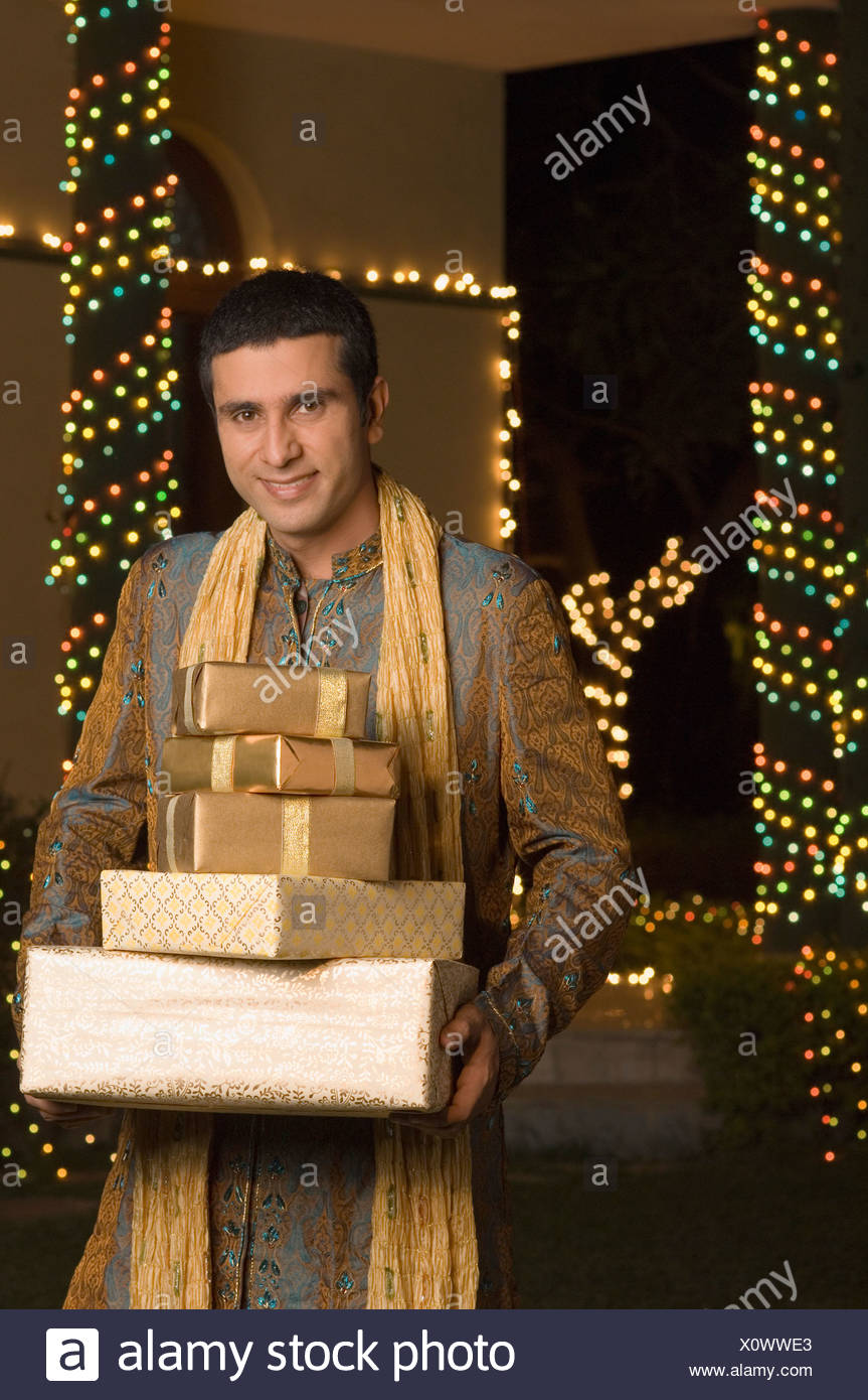 Man holding gifts and smiling Stock Photo: 275934683 - Alamy
