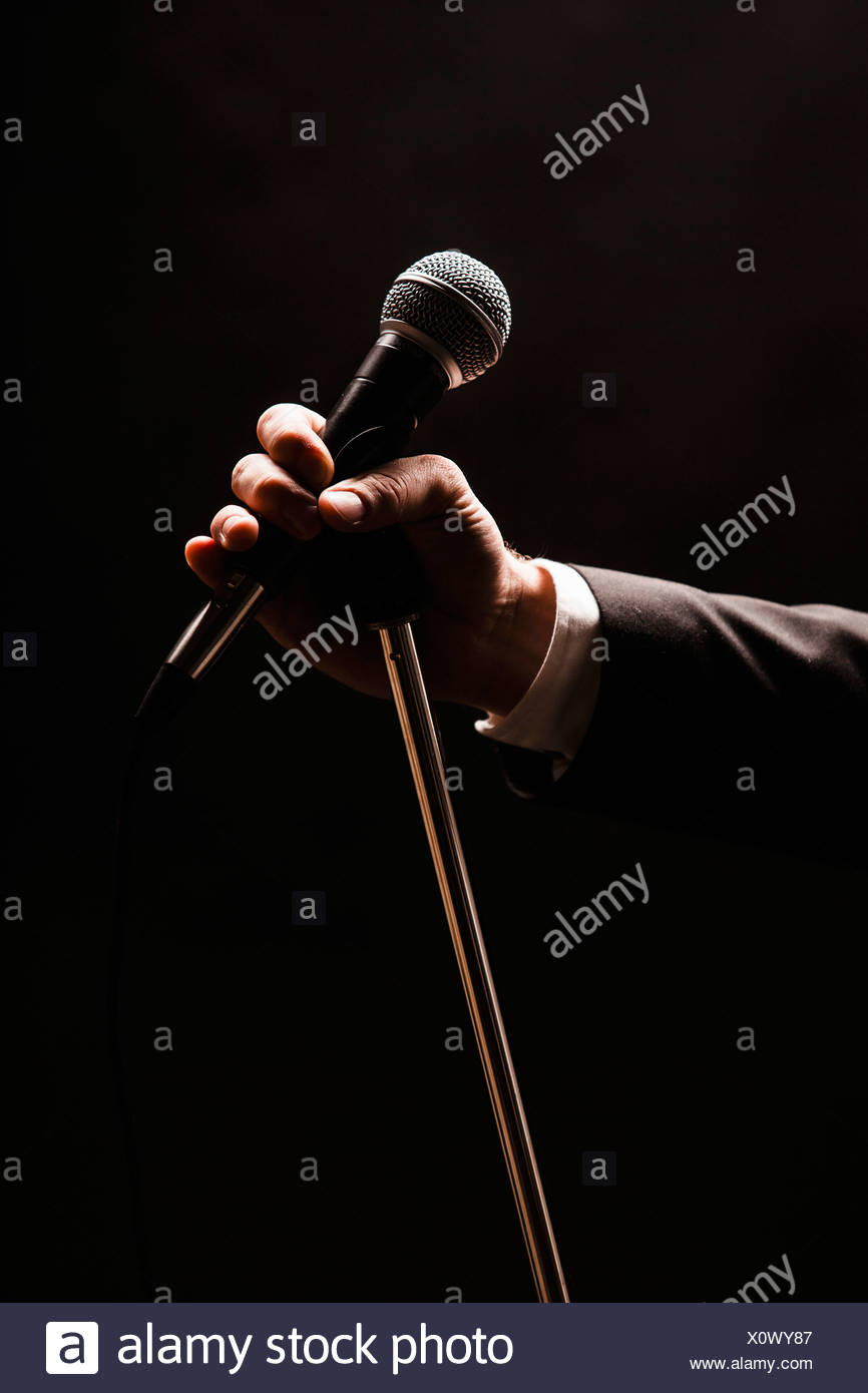 Hand holding microphone over black background - Stock Image