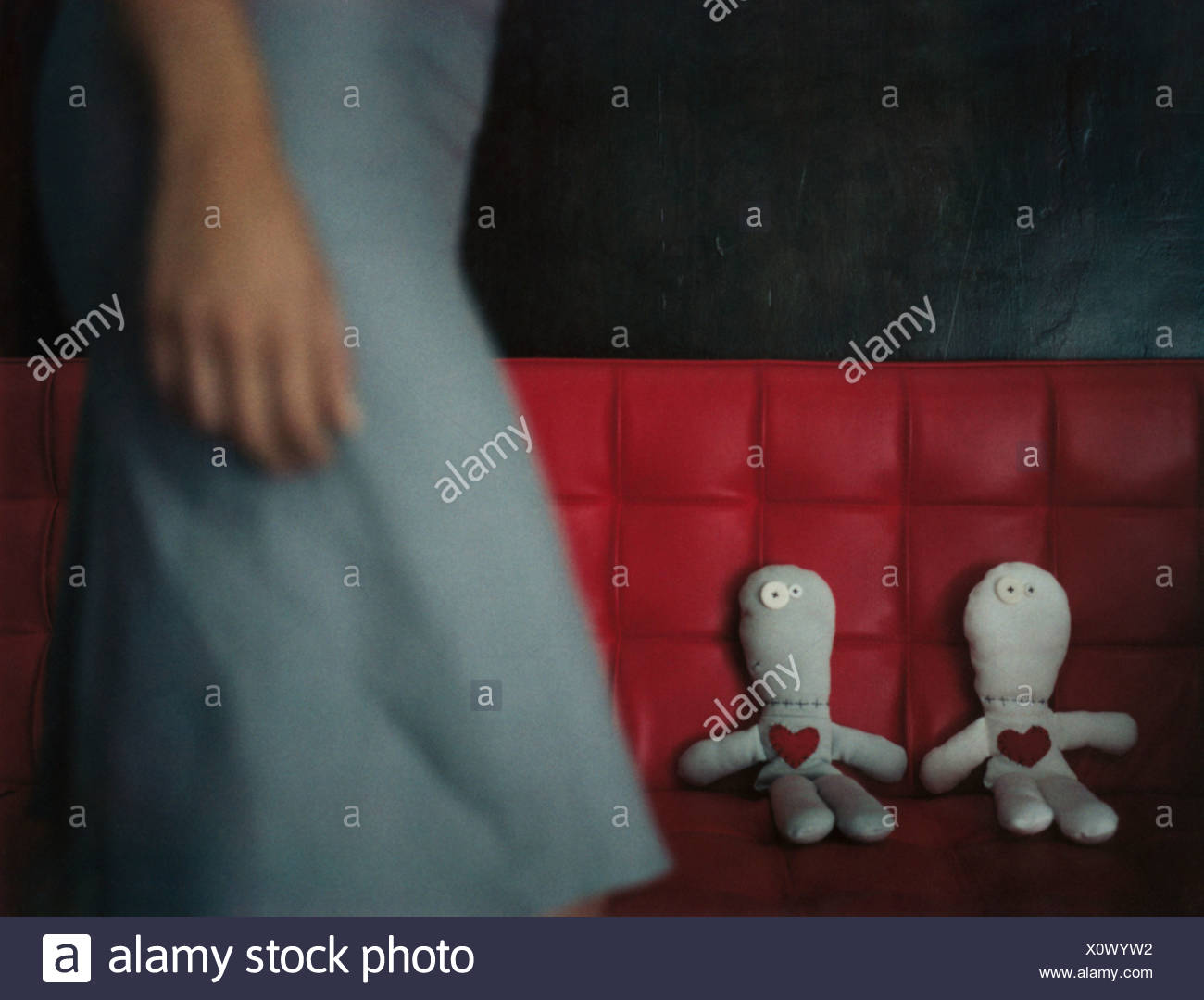 Woman walking by two rag dolls on red sofa, mid section - Stock Image