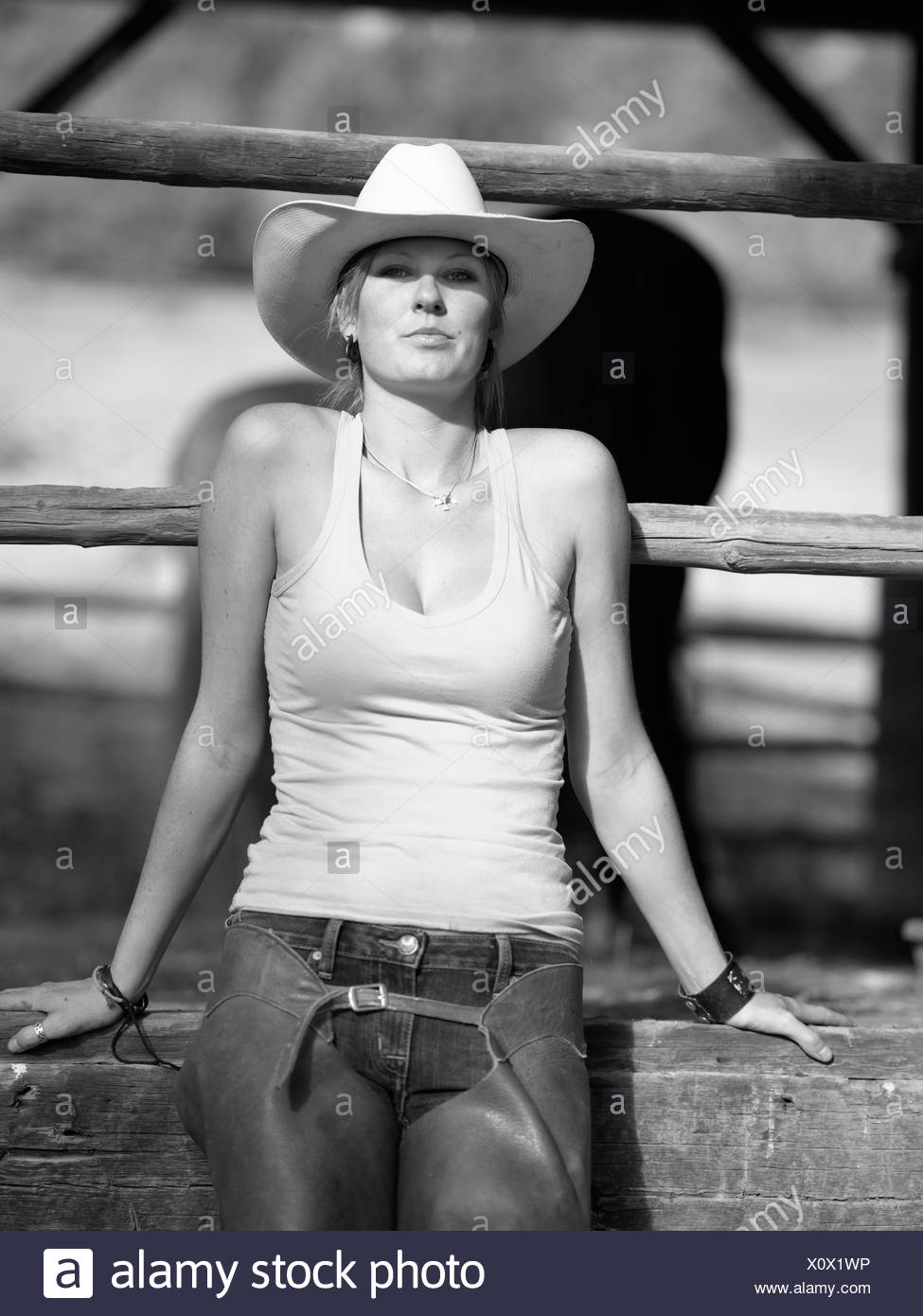 USA, Colorado, Portrait of cowgirl sitting by fence - Stock Image