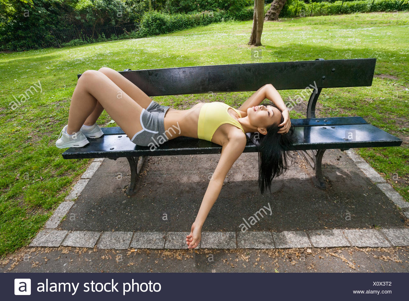Full length of tired fit woman relaxation on beach in park - Stock Image