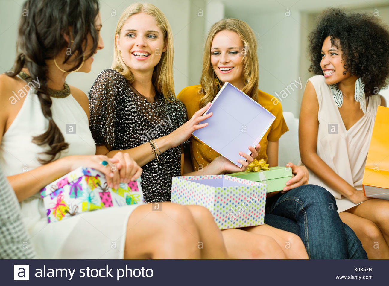 Woman opening gifts at birthday party - Stock Image