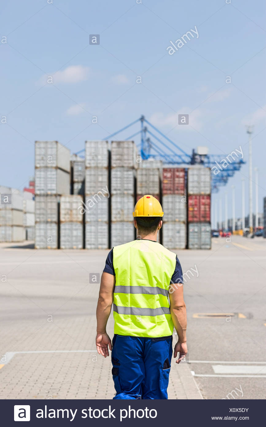 Rear view of mid adult worker walking in shipping yard - Stock Image