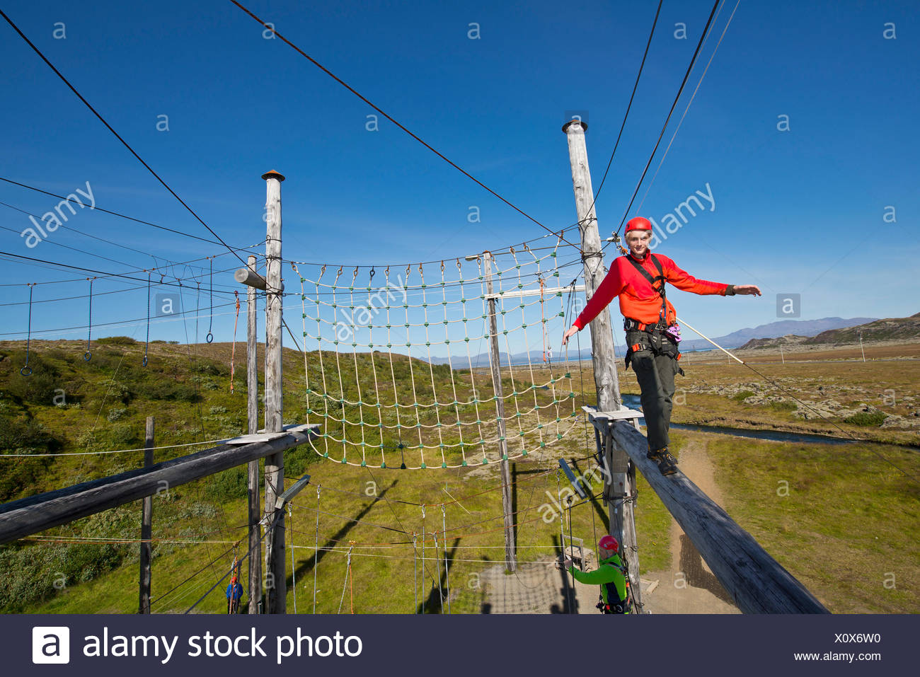 Teenage boy balancing on wooden plank on high rope course - Stock Image