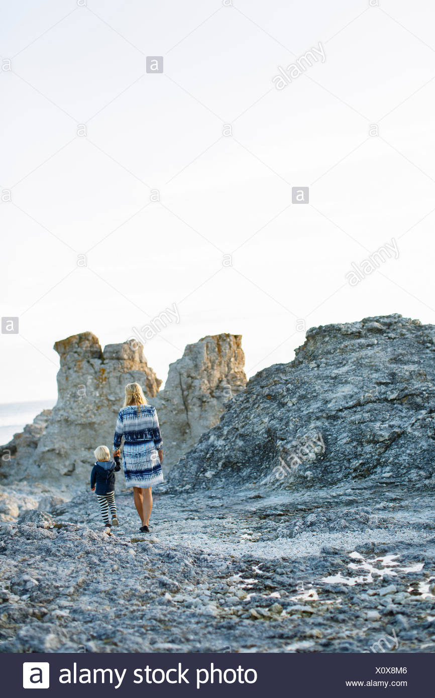 Sweden, Gotland, Faro, Rear view of mother and son (2-3) walking on rocky coast - Stock Image