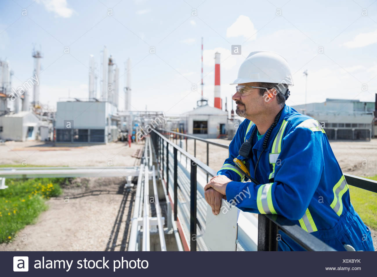 Male worker on platform outside gas plant - Stock Image
