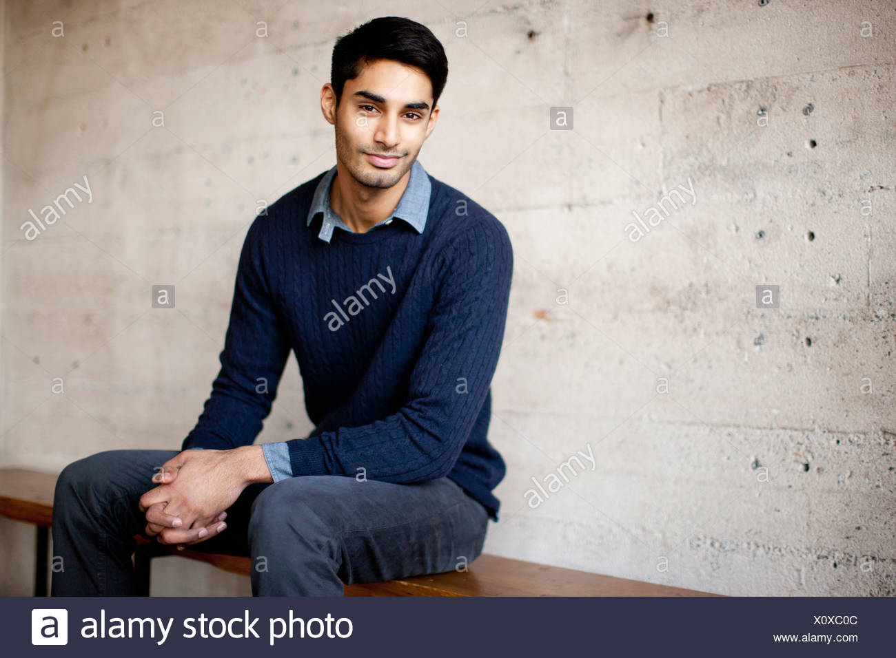 Smiling man sitting on bench - Stock Image