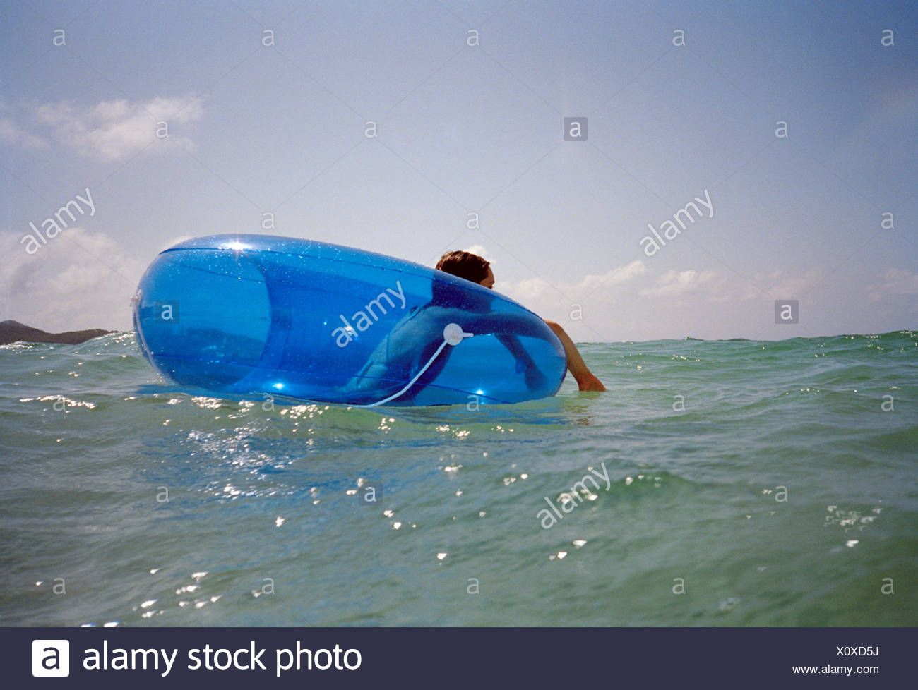 A woman floating on an inner tube in the sea - Stock Image