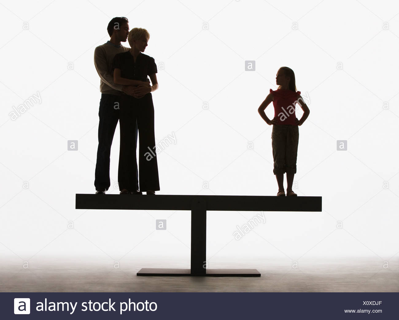 Couple and young girl standing on opposite ends of a plank - Stock Image