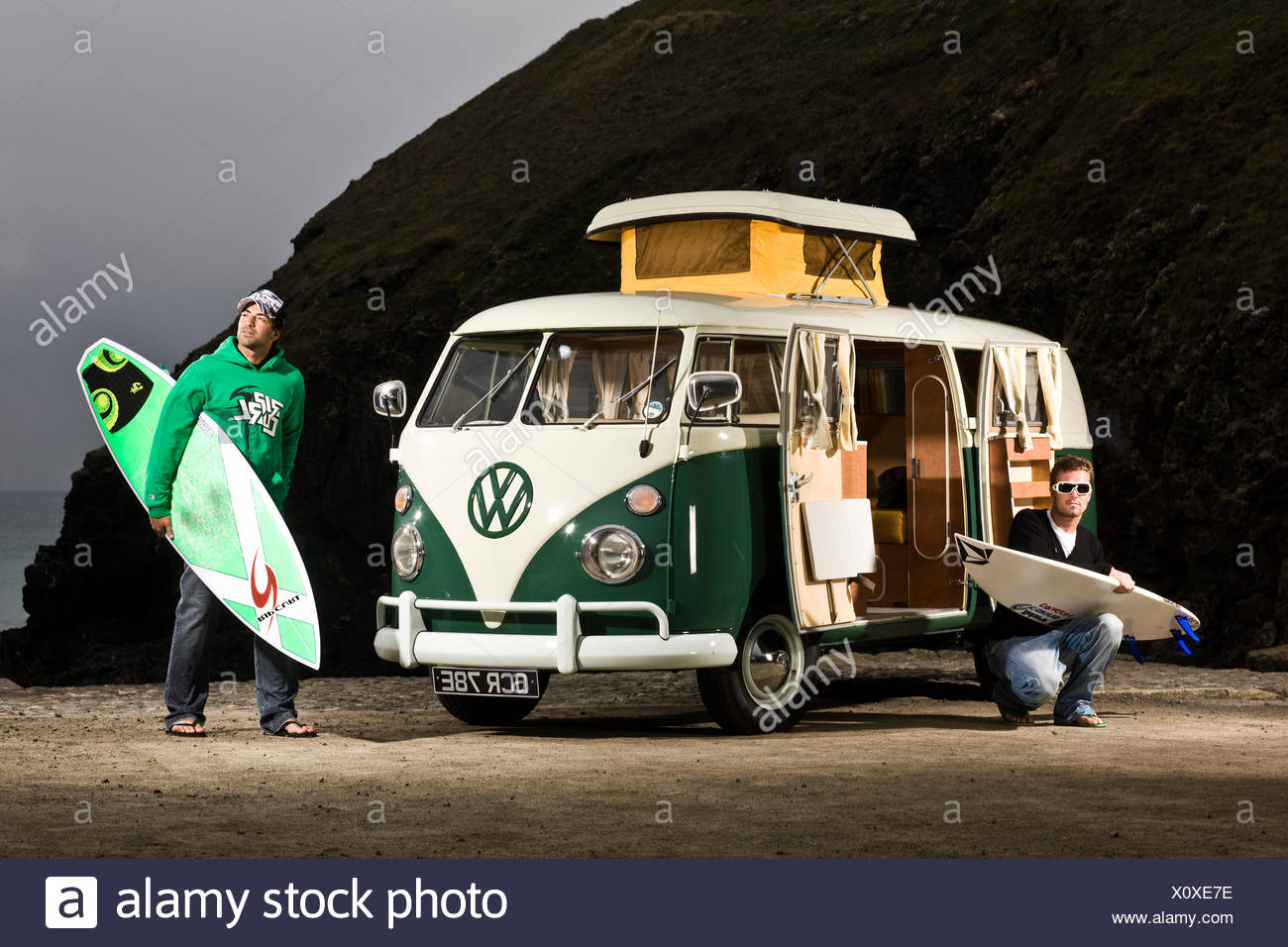 Two surfers with VW campervan, St Agnes, Cornwall, UK - Stock Image