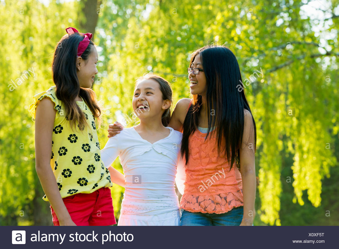 Three girls in park with arms around each other - Stock Image