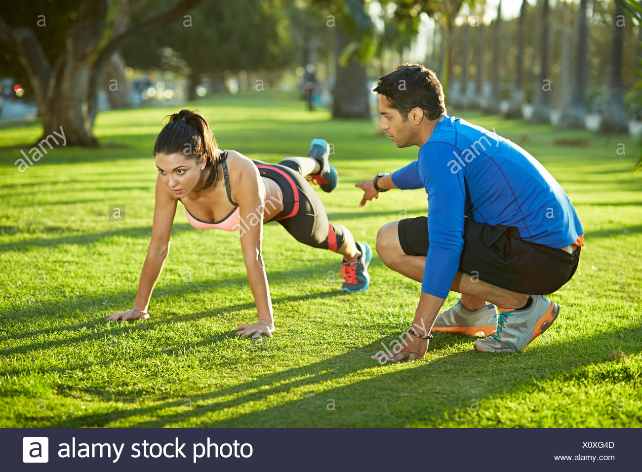 Personal trainer with woman doing plank exercise - Stock Image