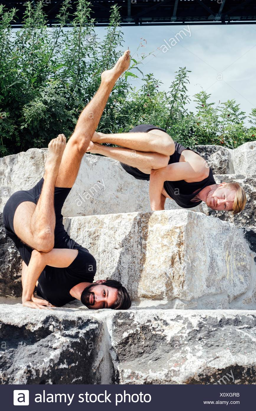 Two men practicing advanced yoga handstand on park step - Stock Image