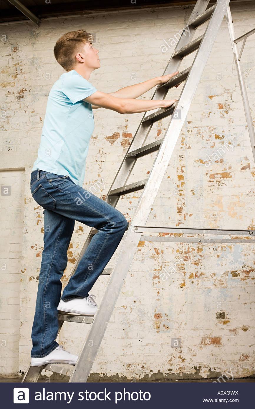 Teenage boy on a ladder - Stock Image