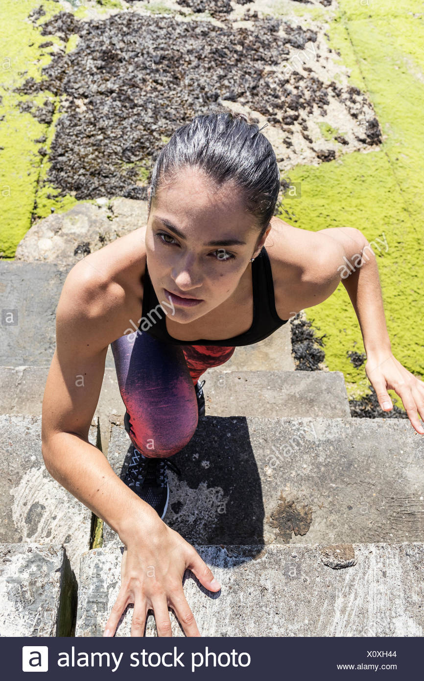 Young female free runner climbing up sea wall - Stock Image