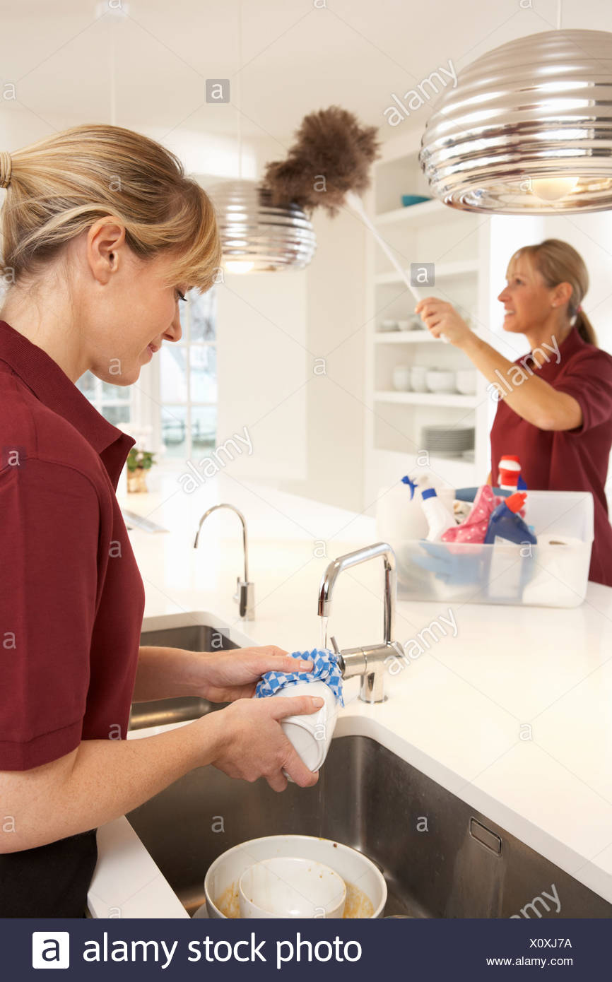 Team Of Commercial Cleaners Working In Domestic Kitchen - Stock Image