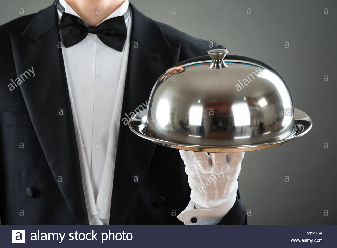 Midsection Of Waiter Holding Tray With Cloche - Stock Image