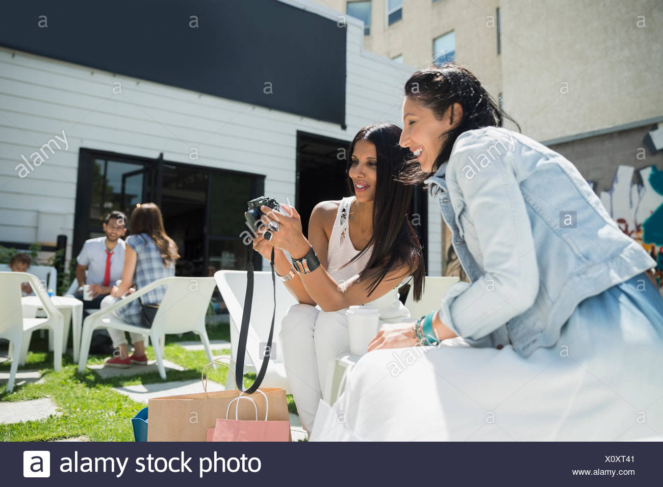 Women viewing photos digital camera on sunny photo - Stock Image