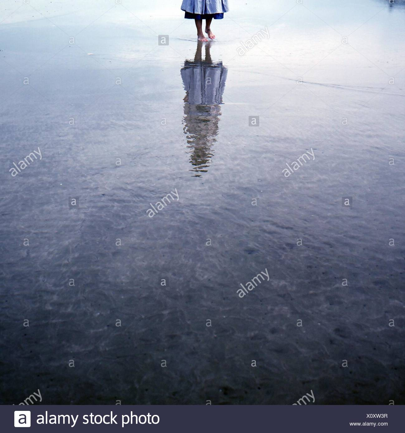 Low Section Of Woman Walking On Water With Reflection Stock Photo