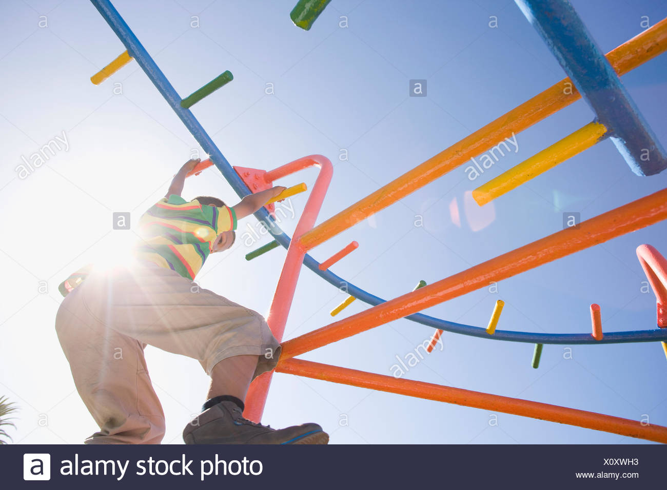 Boy hanging from monkey bars at playground - Stock Image