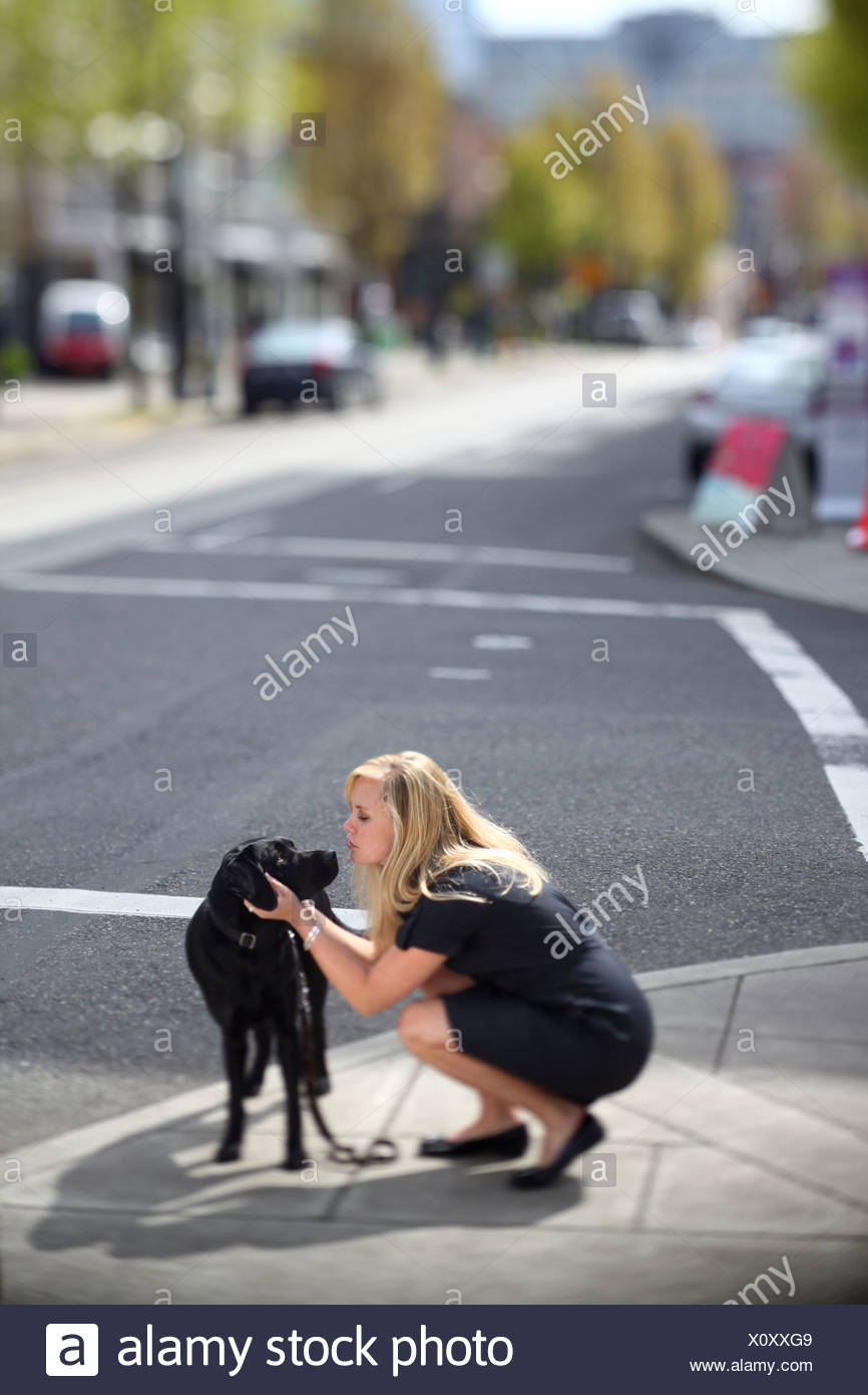 Woman couching on urban sidewalk petting and kissing her dog - Stock Image