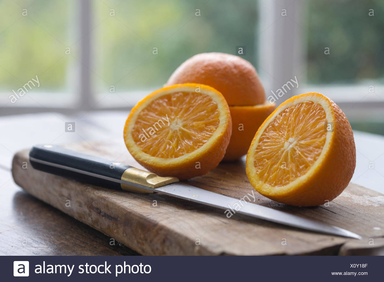 cut oranges on wood baord on table against window framed garden background - Stock Image