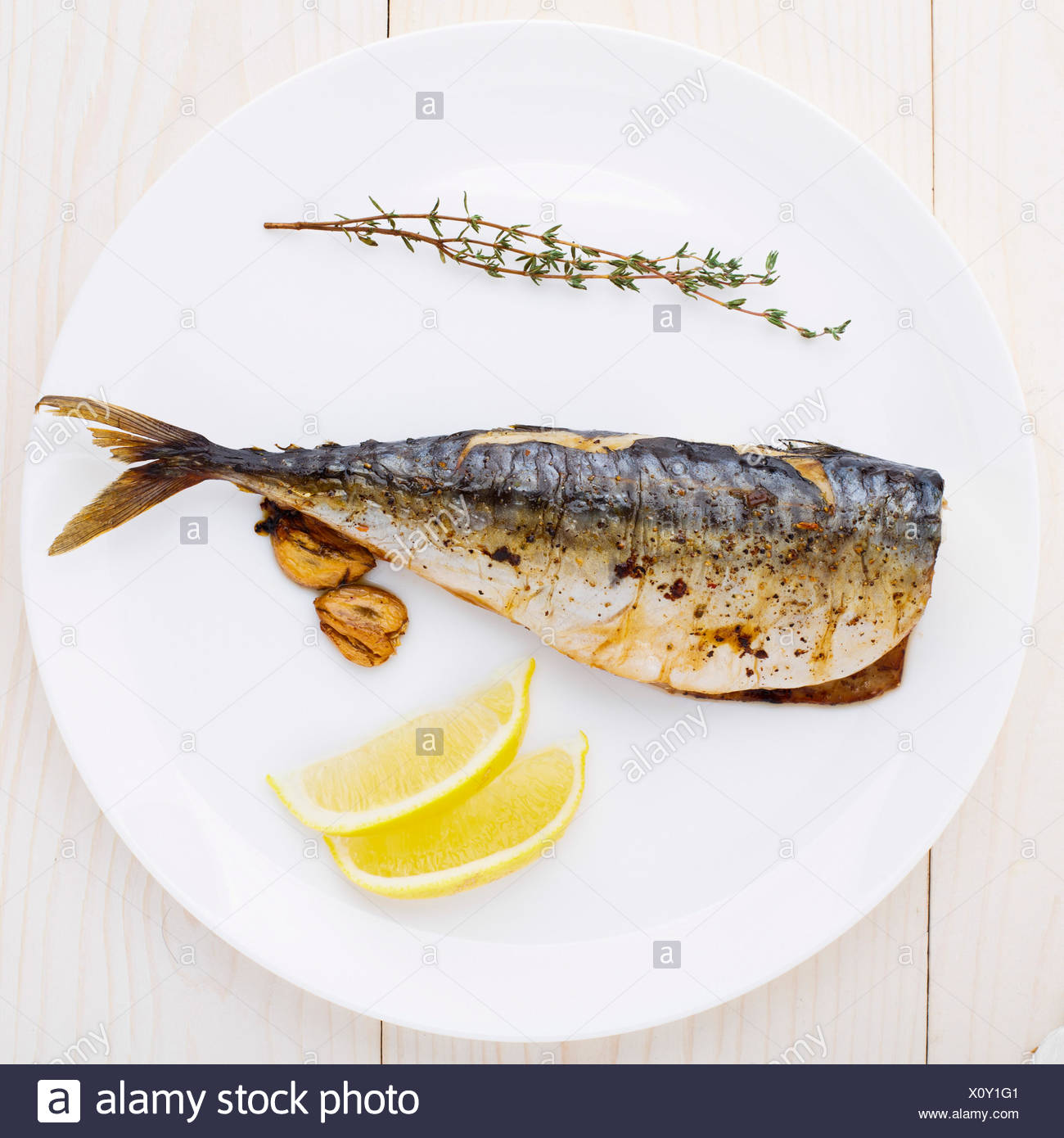 Delicious baked mackerel on a white plate - Stock Image
