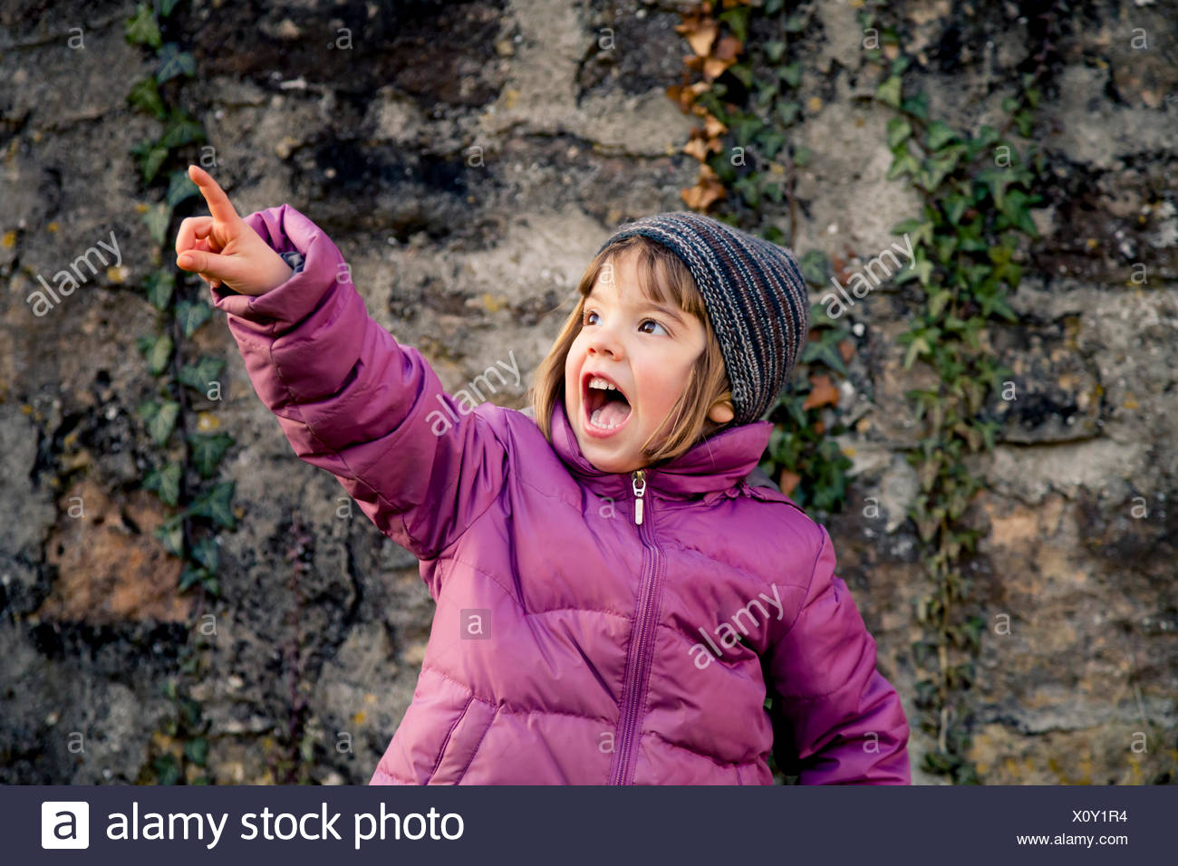 Excited girl wearing woolly hat and pink winter jacket pointing at something - Stock Image