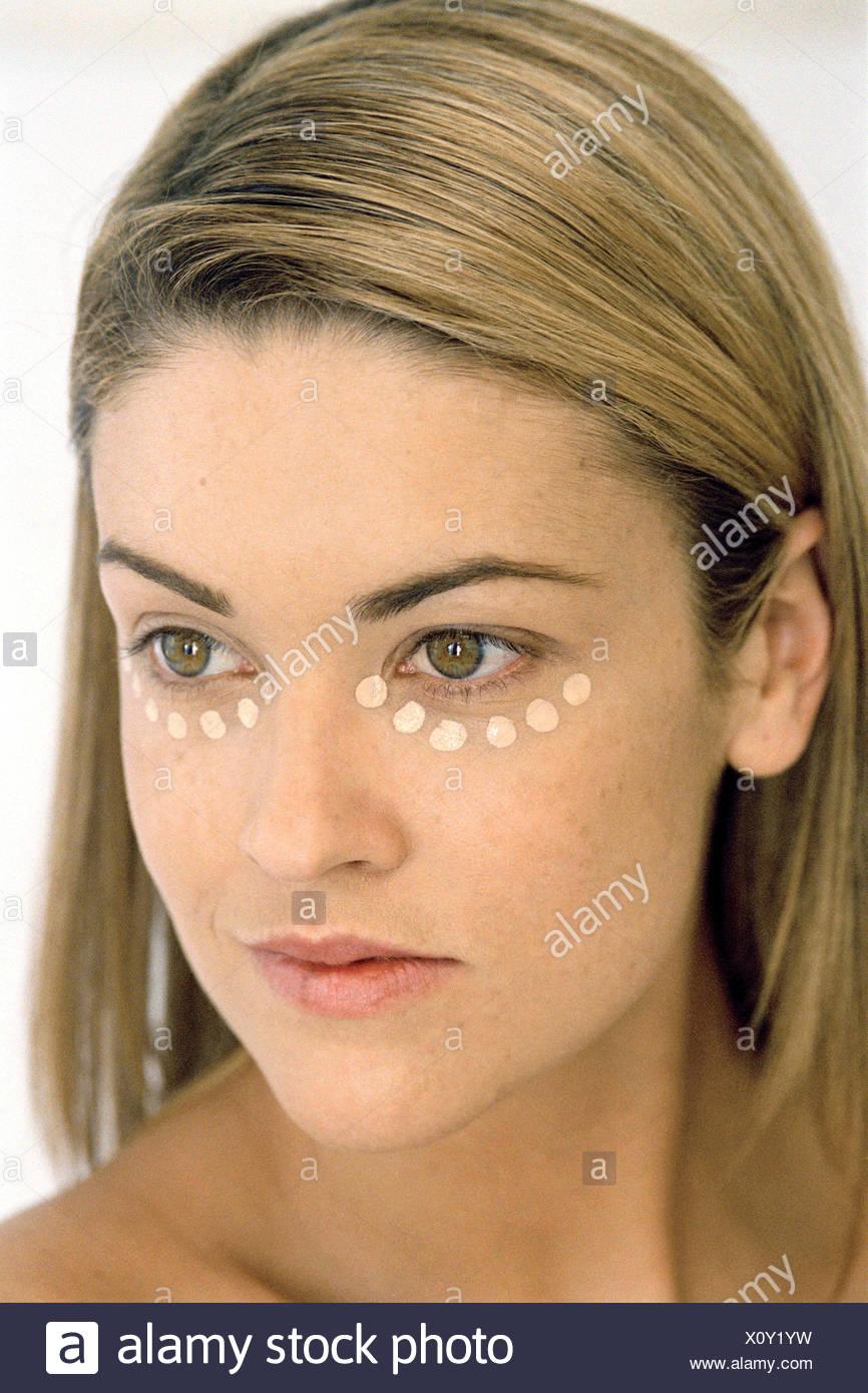 Female straight shoulder length blonde hair side parting tucked behind ears spots of concealer under eye head turned looking - Stock Image